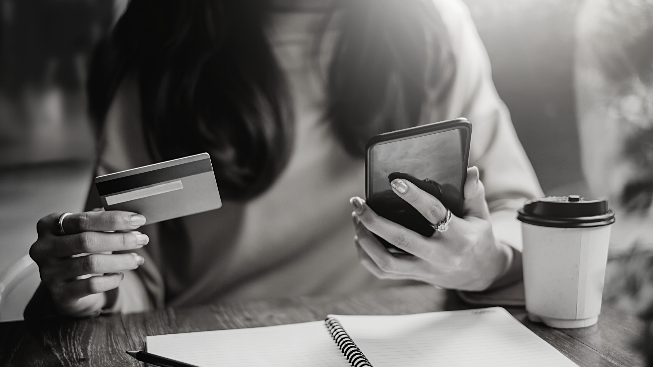 woman holding credit card in one hand and phone in the other