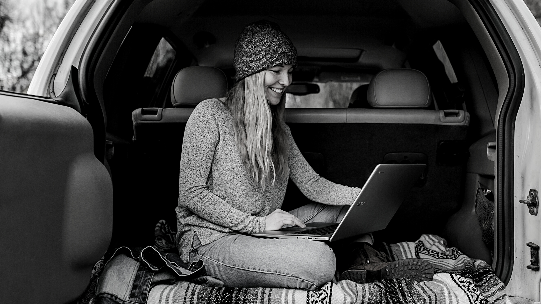 woman sitting in back of vehicle looking at laptop