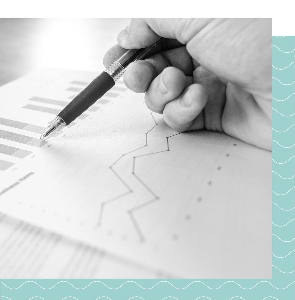 Man's hand holding pen point to data on black and white inbound marketing analytics chart