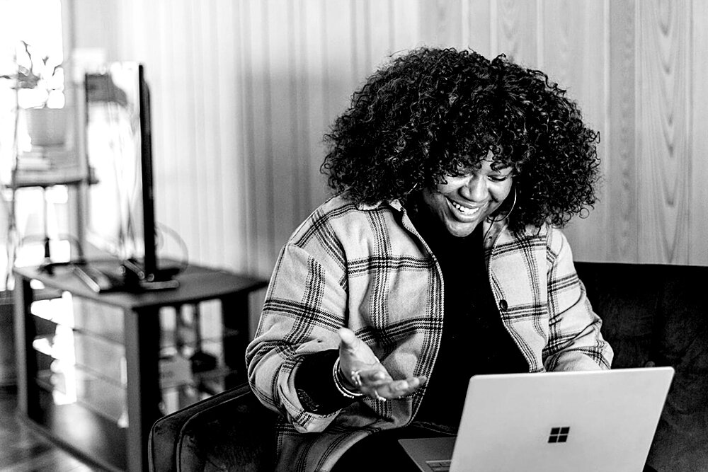Woman happily working on laptop.