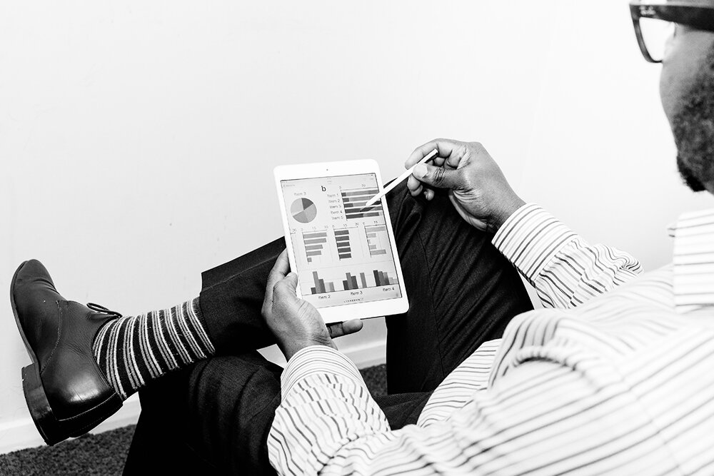 Dapper person sitting with one leg crossed over the other showing their cute striped socks, holding a digital pad with graphs displayed.