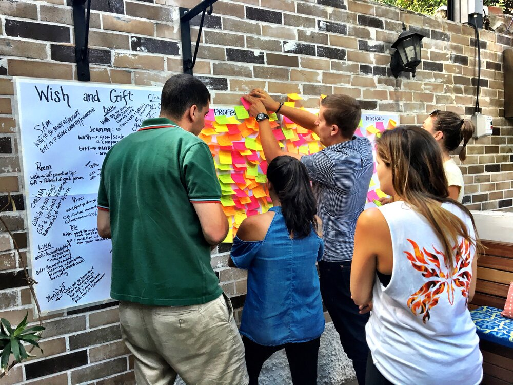 People pinning colorful notes to a board in support of charity work