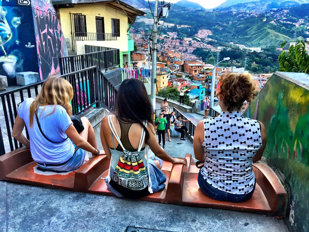 3 women sitting on steps looking out at a colorful view of a town in Colombia