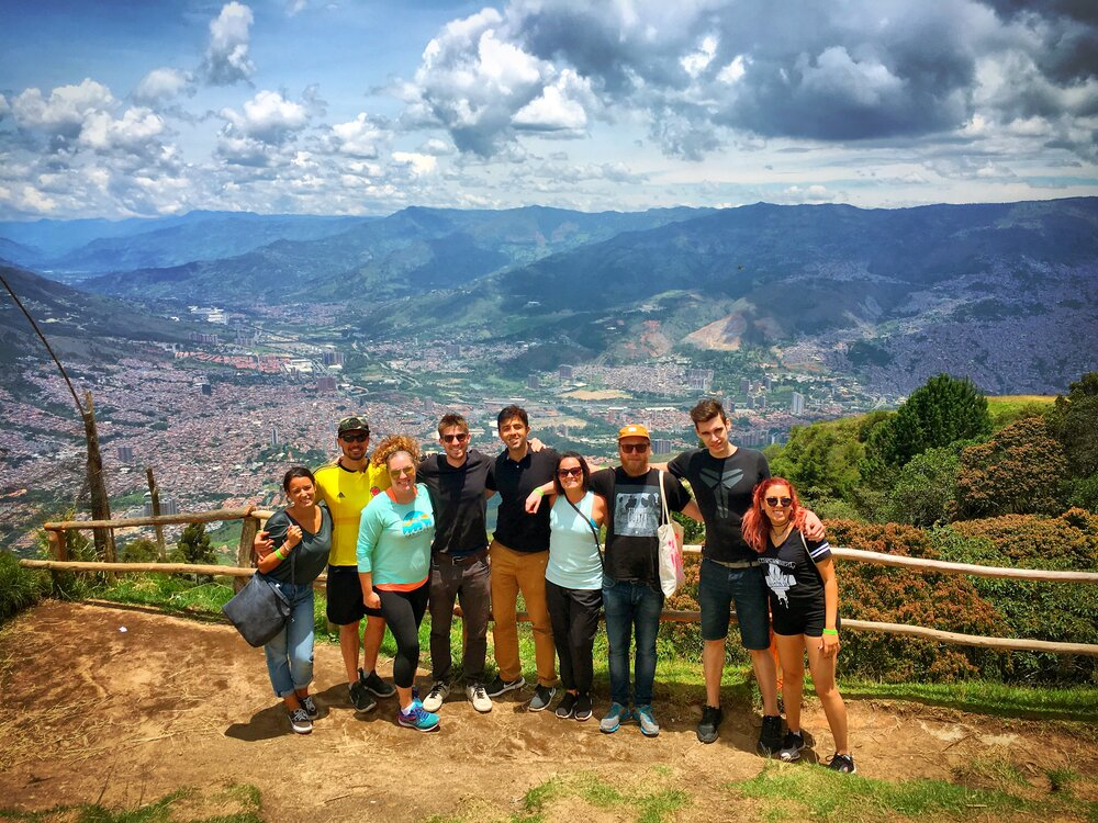 Group of people standing together with a scenic mountain view behind them