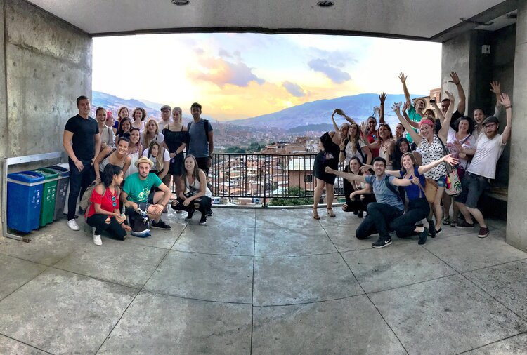 Group of people standing together overlooking a scenic view of a town, mountain range and sunset
