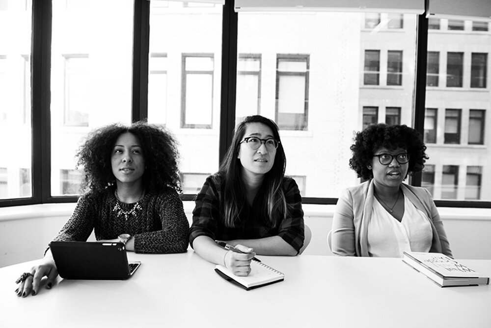 Three culturally diverse women in a business setting.