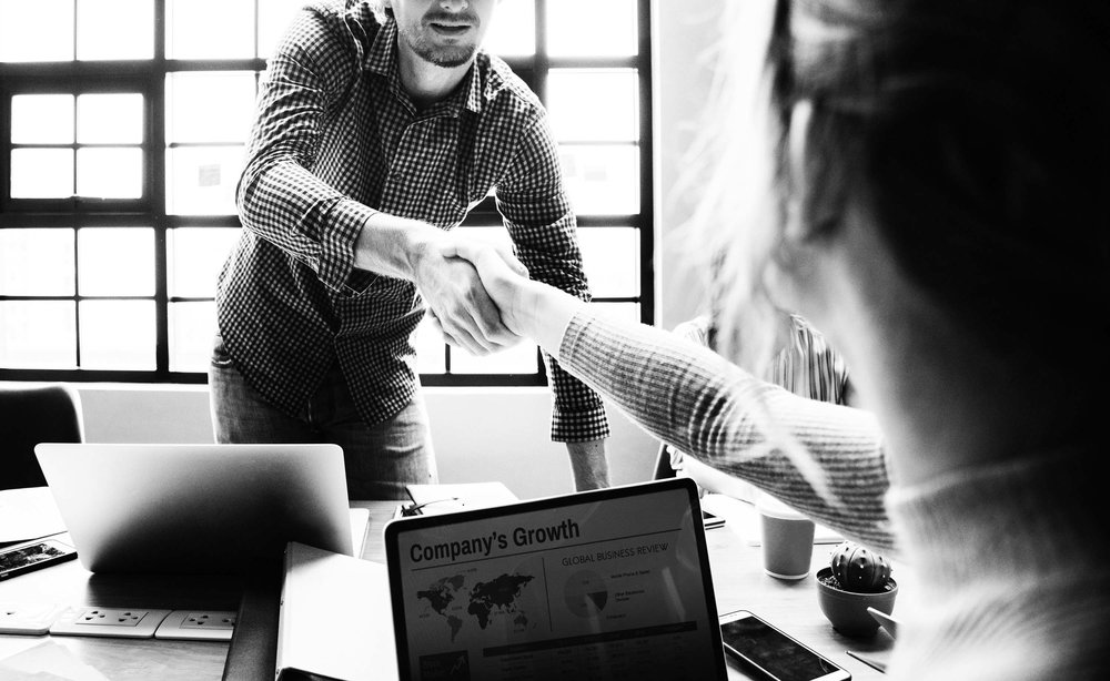 Two businesspeople shaking hands, representative of the relationship between business and customer.