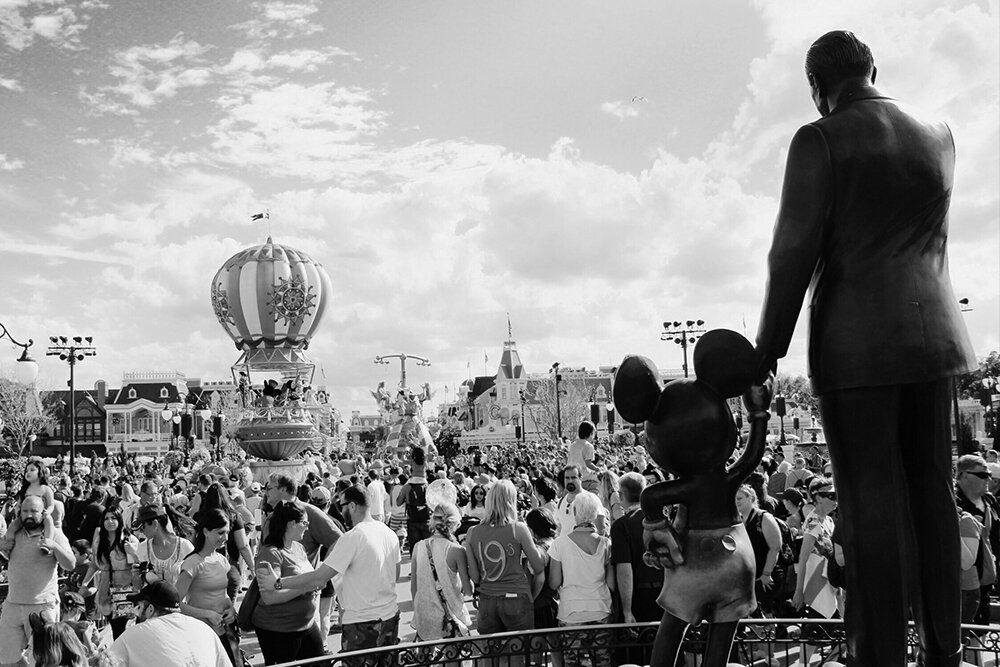 Parade at Disneyworld Orlando with a statue of Walt Disney and Mickey Mouse in the foreground