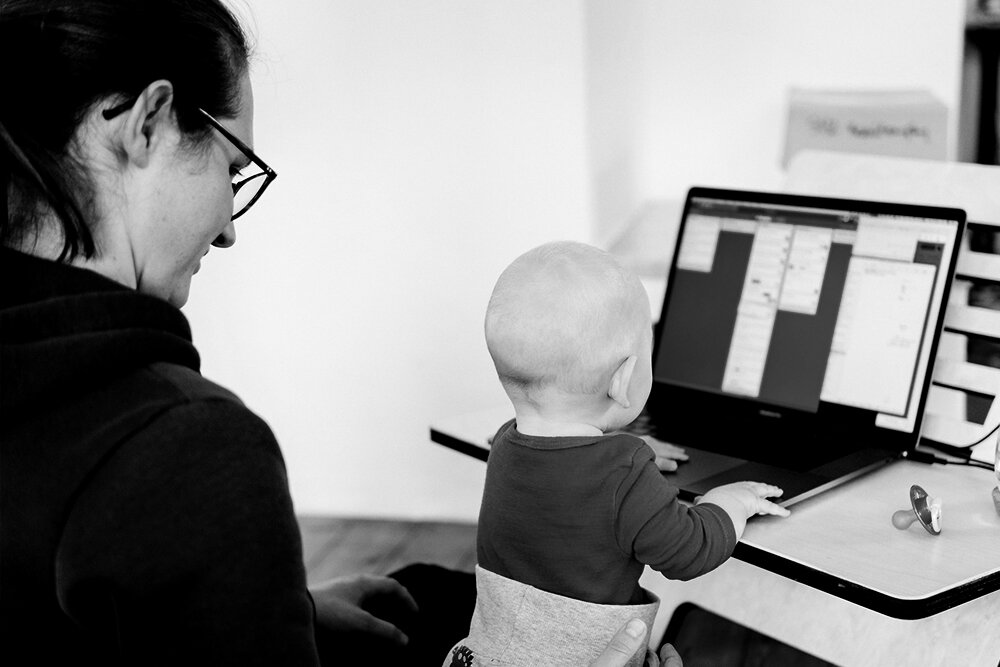 Woman sitting with a baby on her lap, who's playing with a laptop on the desk in front of them.