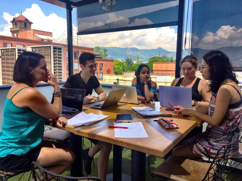 Small group of women and men outside working at a table with laptops and paper with buildings and mountain views in the background