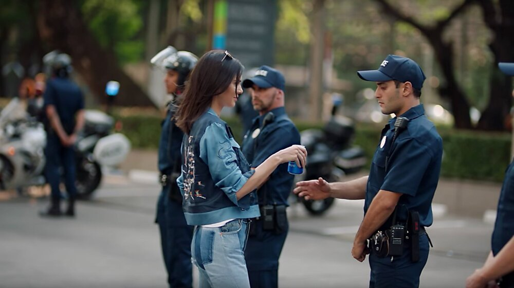 Woman handing a drink to a police officer