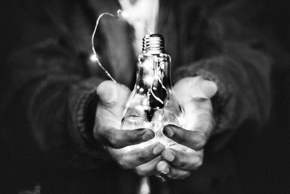 Two hands cradling an illuminated light bulb.