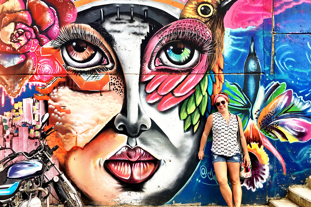 First Page founder, Jeanna Barrett in Colombia standing in front of a colorful mural of a woman's face.