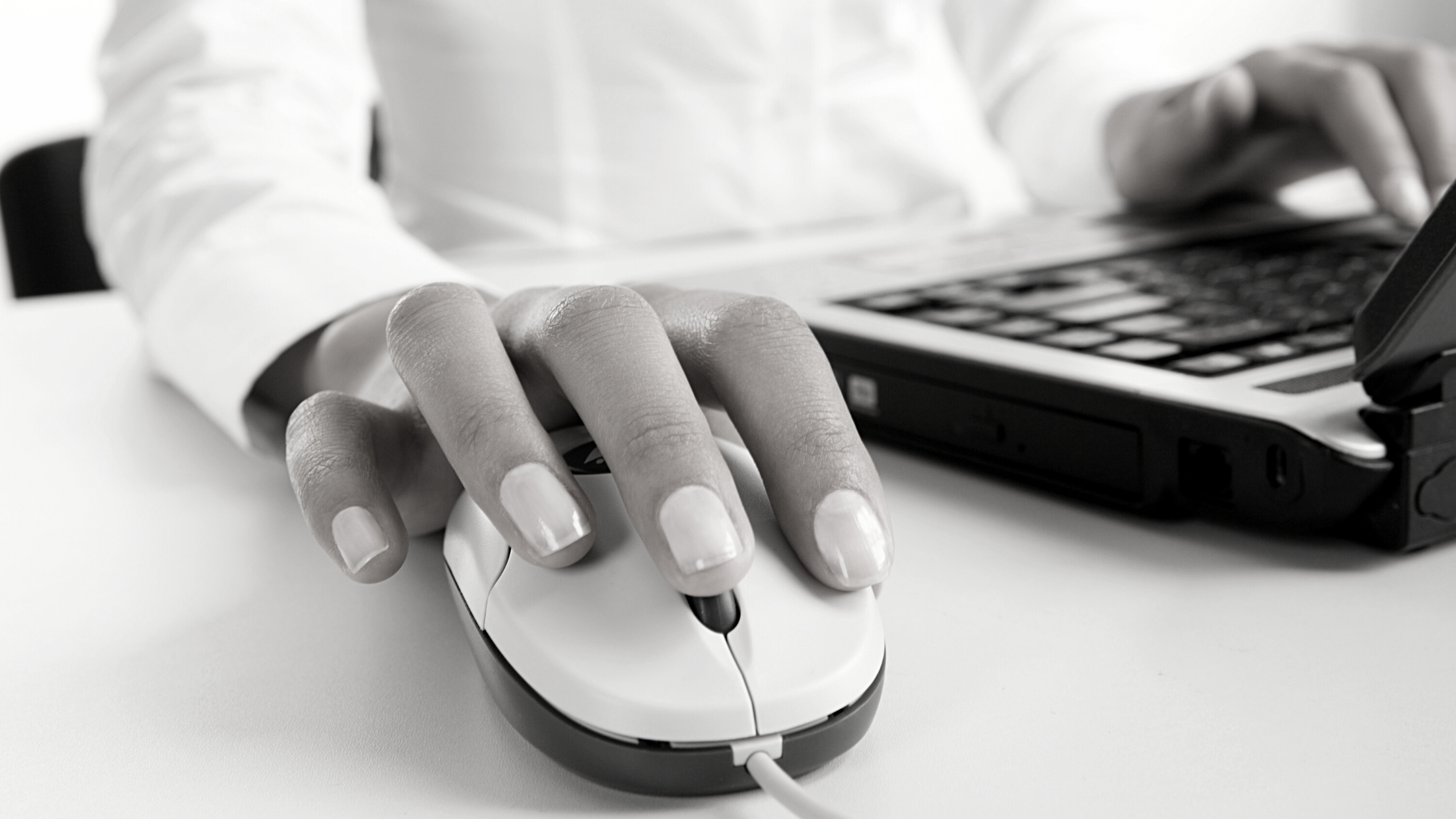 woman's hand resting on computer mouse