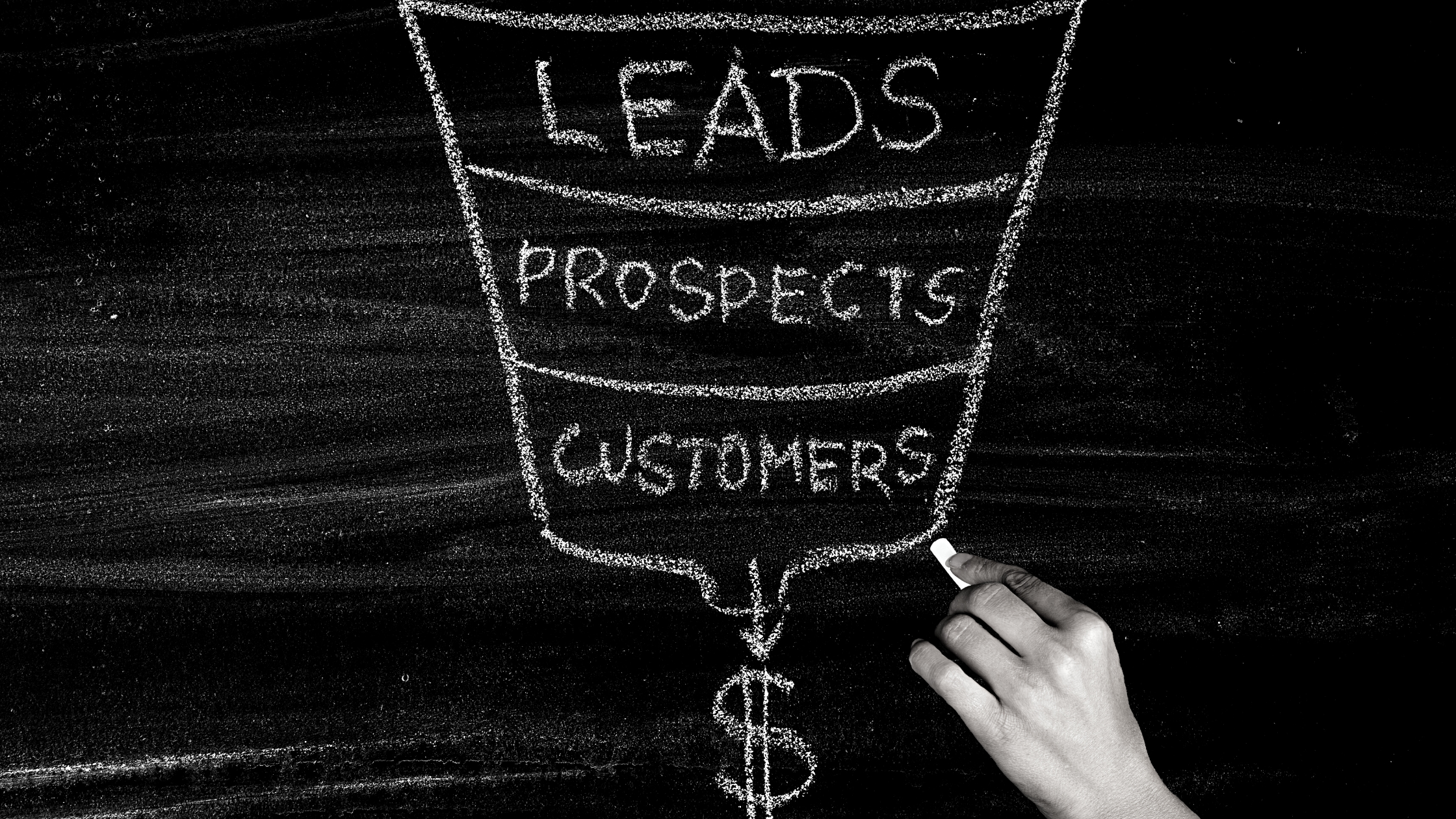 hand using chalk to point to sales funnel on blackboard