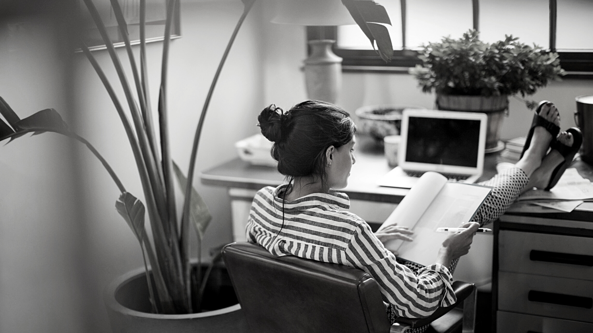 woman sitting at desk with papers in lap and feet on desk