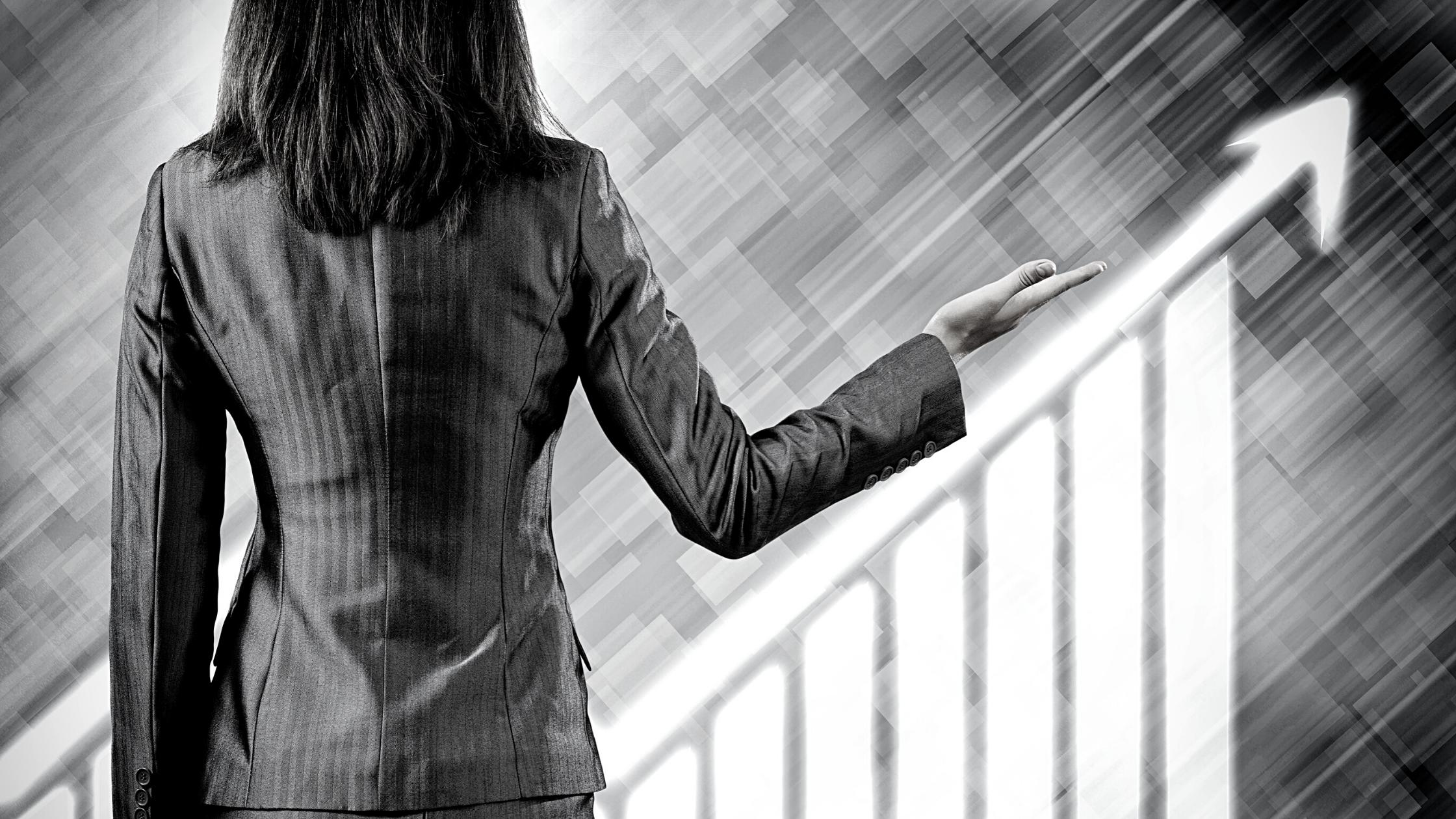 woman standing next to graph moving upward