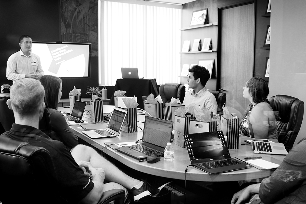 group of people sitting around a conference table with laptops