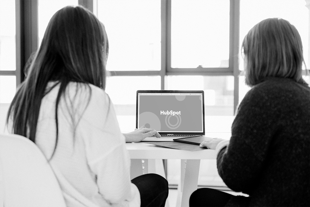two women working on laptop computer showing HubSpot