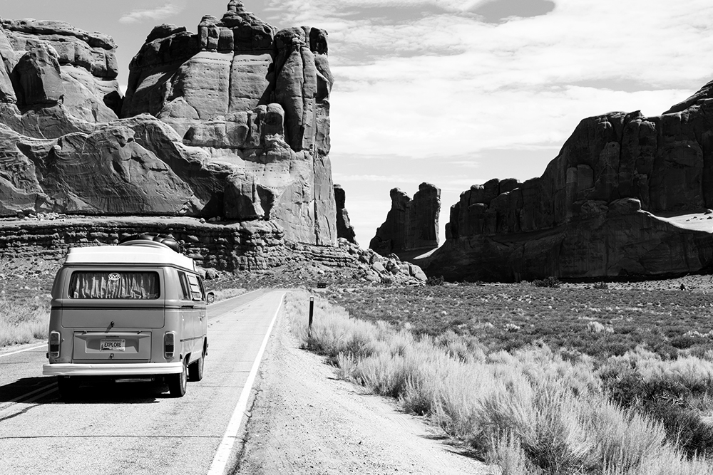 camping van driving down the highway in the desert with rocks and mountains in the background